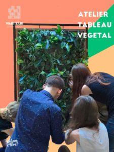 Groupe en train de réaliser un tableau végétal. Vue de dos